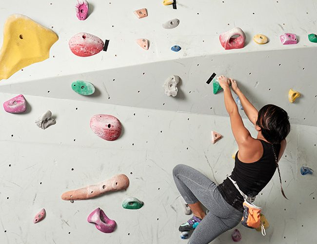 Sporty young woman climbing indoors without belay